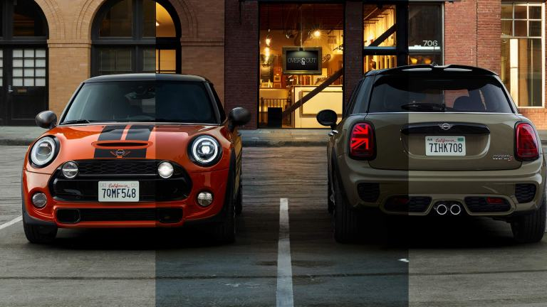 Two new MINI Cooper S hatches parked in front of a stylish looking cafe – one viewed from the front, the other from the rear.